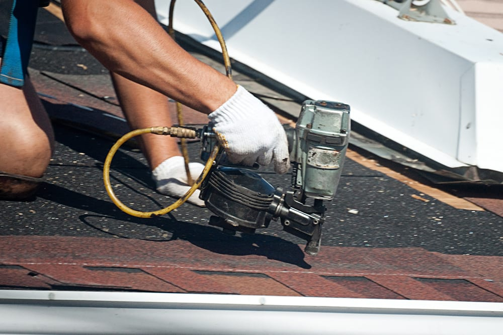 Nailing new shingles onto a roof | commercial painting | Renovia
